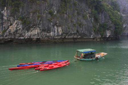 Small boat towing colorful kayaks, Halong Bay, Vietnam photo
