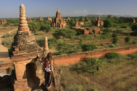 Model released woman admiring view of Bagan temples, Bagan Archaeological Zone, Mandalay region, Myanmar, Southeast Asia Stock Photo