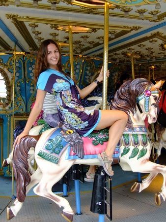 Young woman on merry-go-round carousel photo