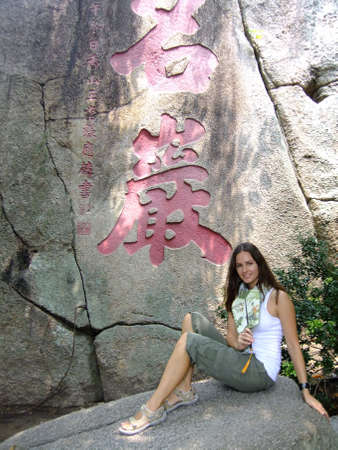 Young woman sitting on a stone with chinese fan, A-Ma temple, Macau photo