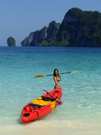 Jonge vrouw in bikini met kajak, Phi Phi Don eiland, Thailand Stockfoto