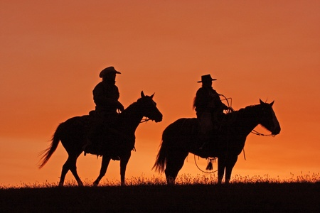 Cowboys on Horseback Silhouette at sunset Stock Photo - 16903684