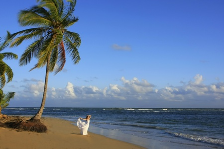 Young woman in white dress on a beach photo