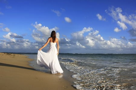 dominican: Young woman in white dress on a beach Stock Photo