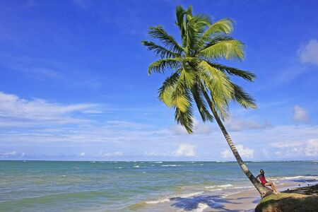 Young woman sitting on a leaning palm tree at Las Terrenas beach, Samana peninsula, Dominican Republic photo