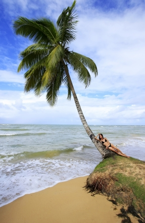 Young woman laying on a leaning palm tree at Las Terrenas beach, Samana peninsula, Dominican Republic photo