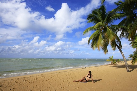 Young woman in bikini sitting at Las Terrenas beach, Samana peninsula, Dominican Republic photo