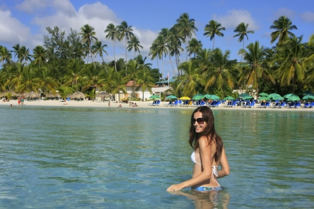 Young woman in bikini standing in clear water, Boca Chica beach, Dominican Republic
