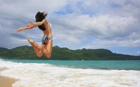Young woman in bikini jumping at Rincon beach, Samana peninsula, Dominican Republic photo