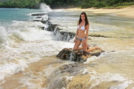 Young woman in bikini sitting on rocks at Rincon beach, Samana peninsula, Dominican Republic Stock fotó
