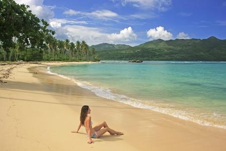 republic of dominican: Young woman in bikini sitting at Rincon beach, Samana peninsula, Dominican Republic