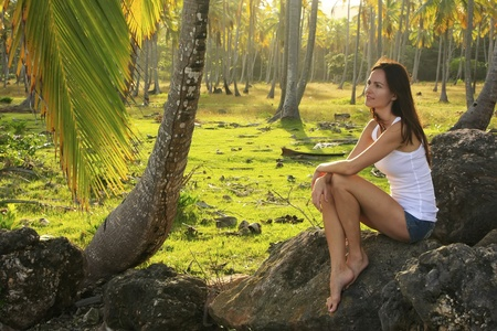 Young woman sitting on rocks in coconut trees grove photo