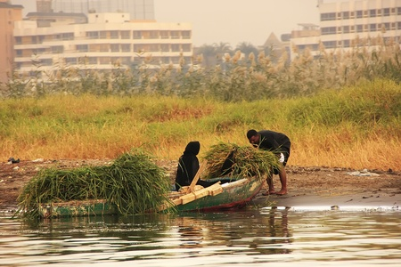 Local people getting into boat on the Nile river, Luxor, Egypt
