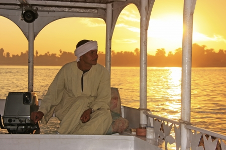 Egyptian captain driving his boat on the Nile river at sunset, Luxor, Egypt Editorial