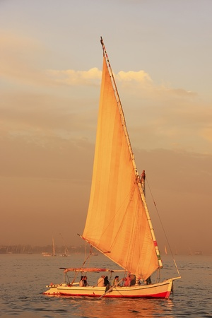 Felucca boat sailing on the Nile river at sunset, Luxor, Egypt photo