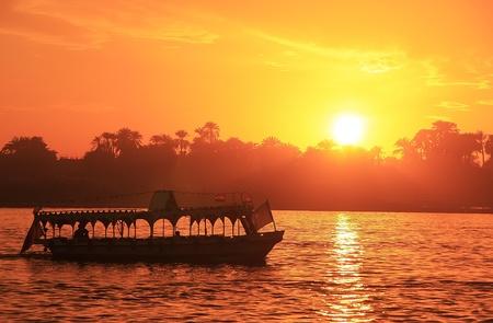 Boot varen de rivier de Nijl bij zonsondergang, Luxor, Egypte