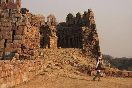 Local guard walking around Tughlaqabad Fort, New Delhi, India