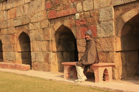 Indian man sitting on a bench at Mausoleum of Ghiyath al-Din Tughluq, Tughlaqabad Fort, New Delhi, India
