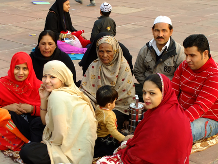 prayer tower: Family sitting in a courtyard of Jama Masjid, Delhi, India