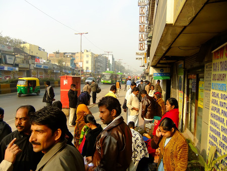 People waiting for bus on the street of Delhi, India