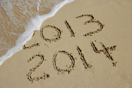 New Year 2014 coming concept, written on a beach with wave photo