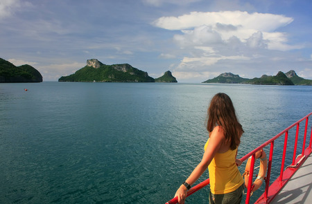 Young woman admiring scene from a boat, Ang Thong National Marine Park , Thailand photo