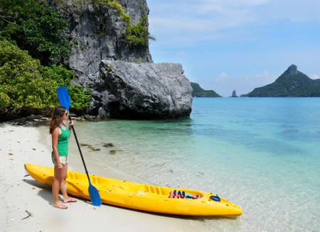 Young woman standing by the kayak, Ang Thong National Marine Park, Thailand photo