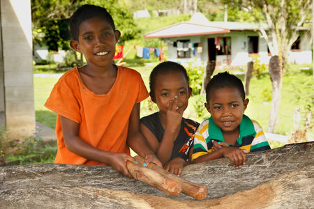 Tree girls standing by the church, Navala village, Viti Levu island, Fiji