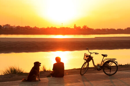 Silhouetted man with a dog watching sunset at Mekong river waterfront, Vientiane, Laos