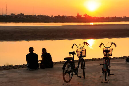 Silhouetted couple watching sunset at Mekong river waterfront, Vientiane, Laos photo