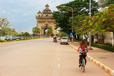 vientiane: Young woman riding bike near Victory Gate Patuxai, Vientiane, Laos Stock Photo