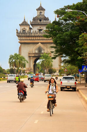 laotian: Young woman riding bike near Victory Gate Patuxai, Vientiane, Laos Stock Photo