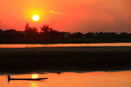 Silhouetted boat on Mekong river at sunset, Vientiane, Laos, Southeast Asia photo