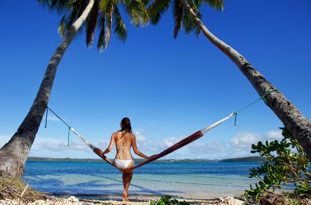 tonga: Young woman in bikini sitting in a hammock between palm trees, Ofu island, Vavau group, Tonga Stock Photo
