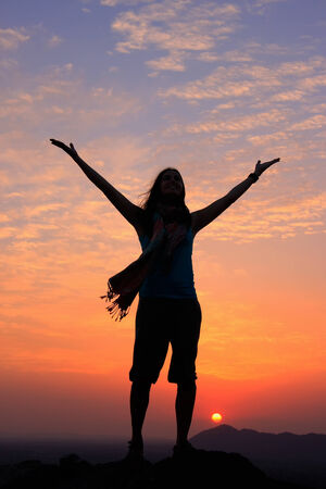 Sillouetted woman with her arms up at sunset on top of the hill, Pushkar, Rajasthan, India photo
