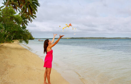 Young woman on a beach throwing flowers in the air, Ofu island, Tonga