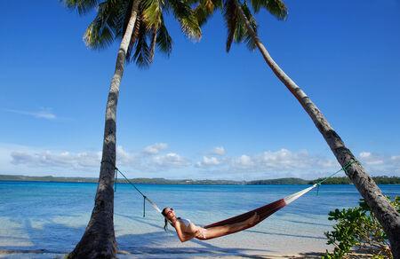 Young woman in bikini laying in a hammock between palm trees, Ofu island, Vavau group, Tonga photo