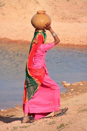 Mujer local llevando la jarra con agua sobre su cabeza, pueblo Khichan, Rajasthan, India