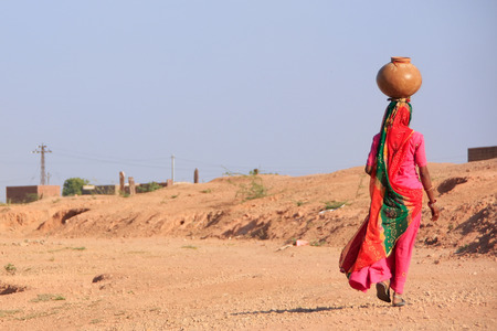 Local woman carrying jar with water on her head, Khichan village, Rajasthan, India