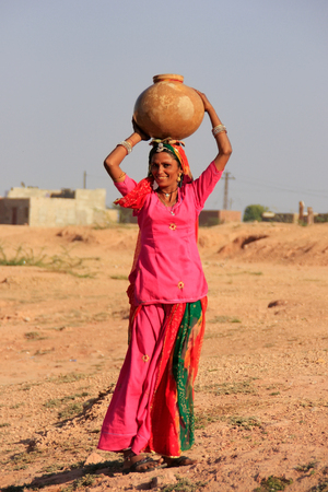 carrying: Local woman carrying jar with water on her head, Khichan village, Rajasthan, India