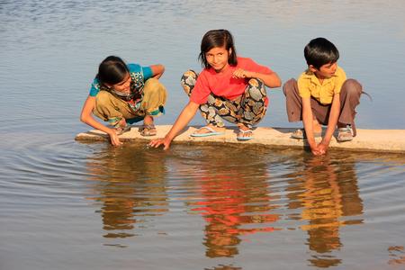 Lokale kinderen drinken van water reservoir, Khichan dorp, Rajasthan, India Redactioneel