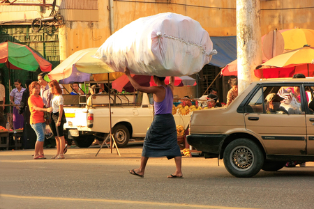 carying: Local man carrying big bag with goods on his head, Yangon, Myanmar, Southeast Asia
