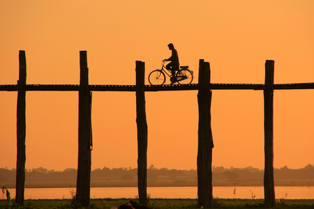 Silhouetted person with a bike on U Bein Bridge at sunset, Amarapura, Mandalay region, Myanmar