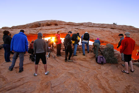 moab: Photographers and tourists watching sunrise at  Mesa Arch, Canyonlands National Park, Utah