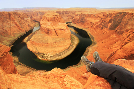 Pair of legs at Horseshoe bend overlook, adventure concept  photo