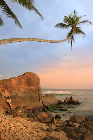 Woman pose at the rock near Leaning palm tree with big rocks, Unawatuna beach, Sri Lanka photo
