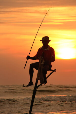 Silhouette of a stick fisherman at sunset, Unawatuna, Sri Lanka photo