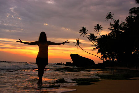 Silhouetted woman on a beach with palm trees and rocks at sunset, Unawatuna, Sri Lanka photo