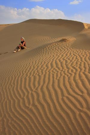 Young woman sitting on dunes, Thar desert, Jaisalmer, Rajasthan, India photo