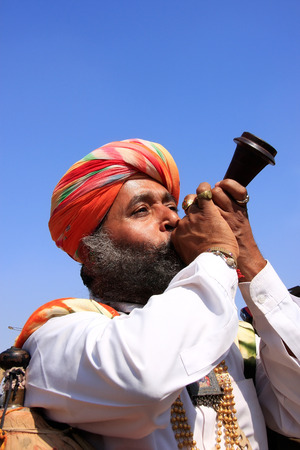 Indian man blowing horn during Mr Desert competition, Jaisalmer, Rajasthan, India